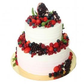 Белый двухъярусный свадебный торт со свежими ягодами на каждом ярусе