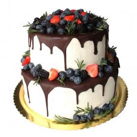 Белый двухъярусный свадебный торт, политый темным шоколадом и украшенный свежими ягодами