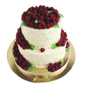 Белый двухъярусный свадебный торт, украшенный листьями из мастики и свежей малины