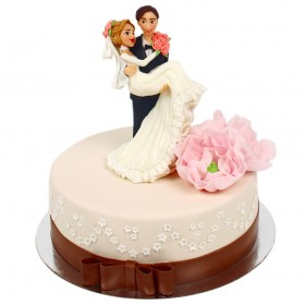Белый одноярусный свадебный торт с коричневой лентой на ярусе,  украшенный розовыми пионами и фигурками жениха с невестой