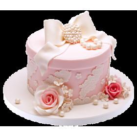Торт в форме подарочной коробки розового цвета украшен бантом из мастики и жемчужинами из белого шоколада