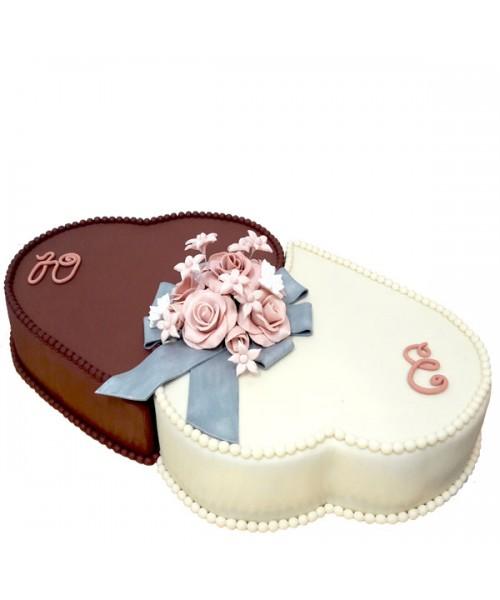 Торт праздничный в форме двух сердца белого и темного цвета украшен букетом цветов