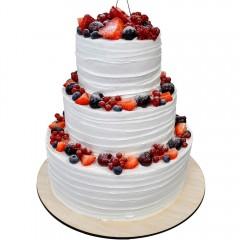 Трехъярусный свадебный торт в белом цвете украшен свежими ягодами клубники, малины, черники