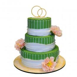 Трехъярусный свадебный торт в зеленом цвете украшенный пышными бутонами живых цветов и фигурками обручальных колец